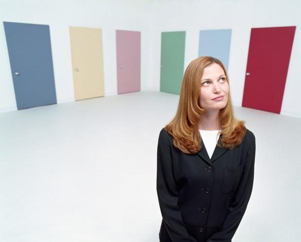 ca. 2001 --- Businesswoman in Front of Doors --- Image by © Royalty-Free/Corbis