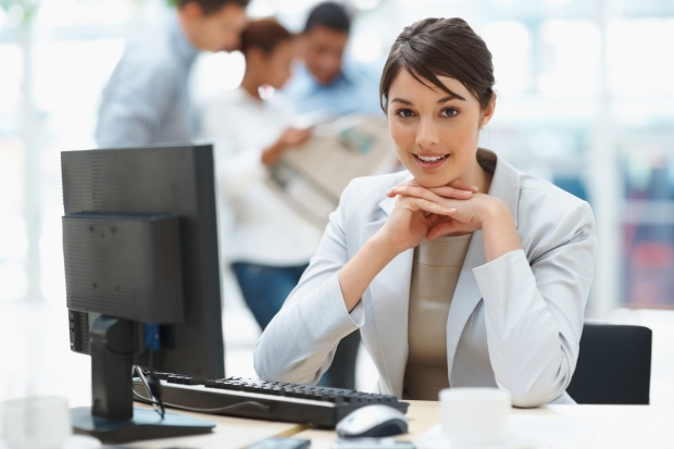 Pretty Caucasian business woman at office desk with colleagues in the back
